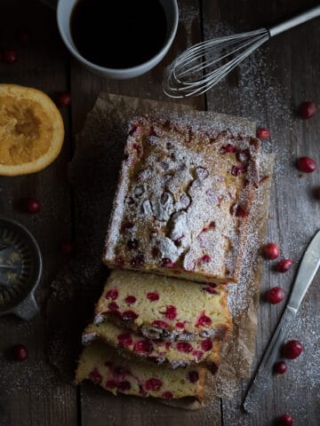 Overhead on the delicious Homemade Cranberry Orange Bread with lots of cranberries around on the table