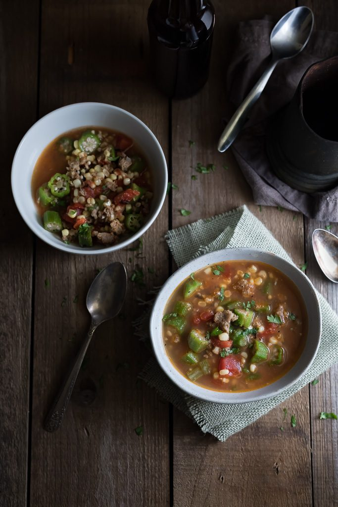 Hearty Vegetable and Sausage Soup served in two white bowls on a wooden surface with two metal spoons on the side