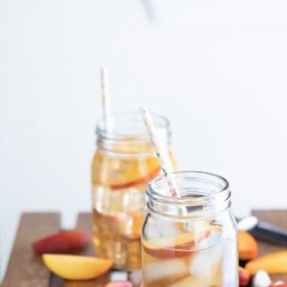 Georgia Peach Cocktail served in two glass jars with cute straws inside each jar