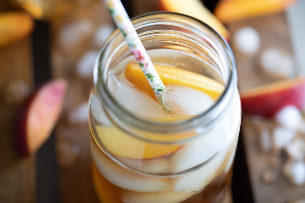 Closeup of the delicious Georgia Peach Cocktail with a cute straw inside the jar