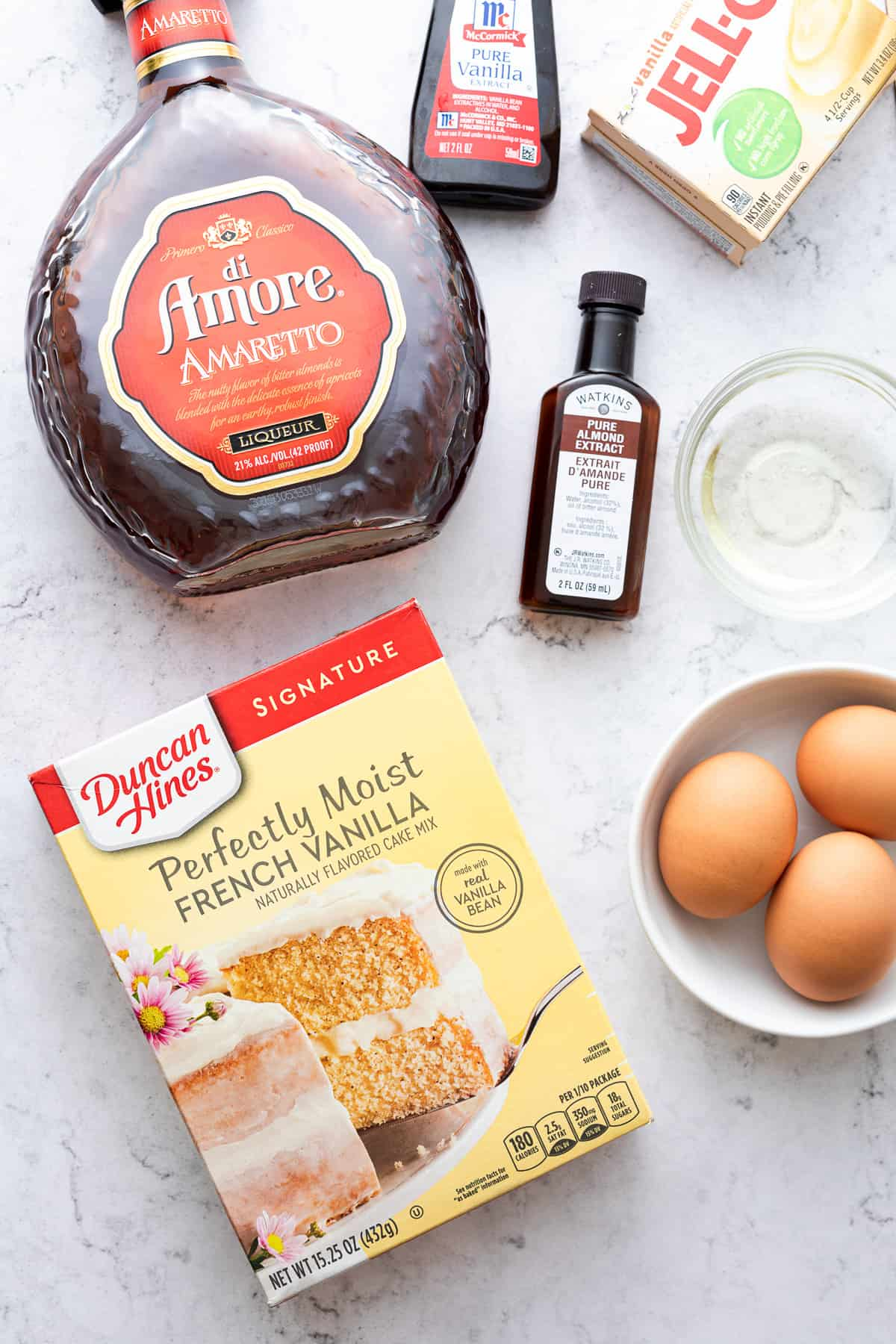 Amaretto Bundt Cake ingredients, including eggs, cake mix, pure almond extract and Amaretto liqueuer, showcased on a big white countertop