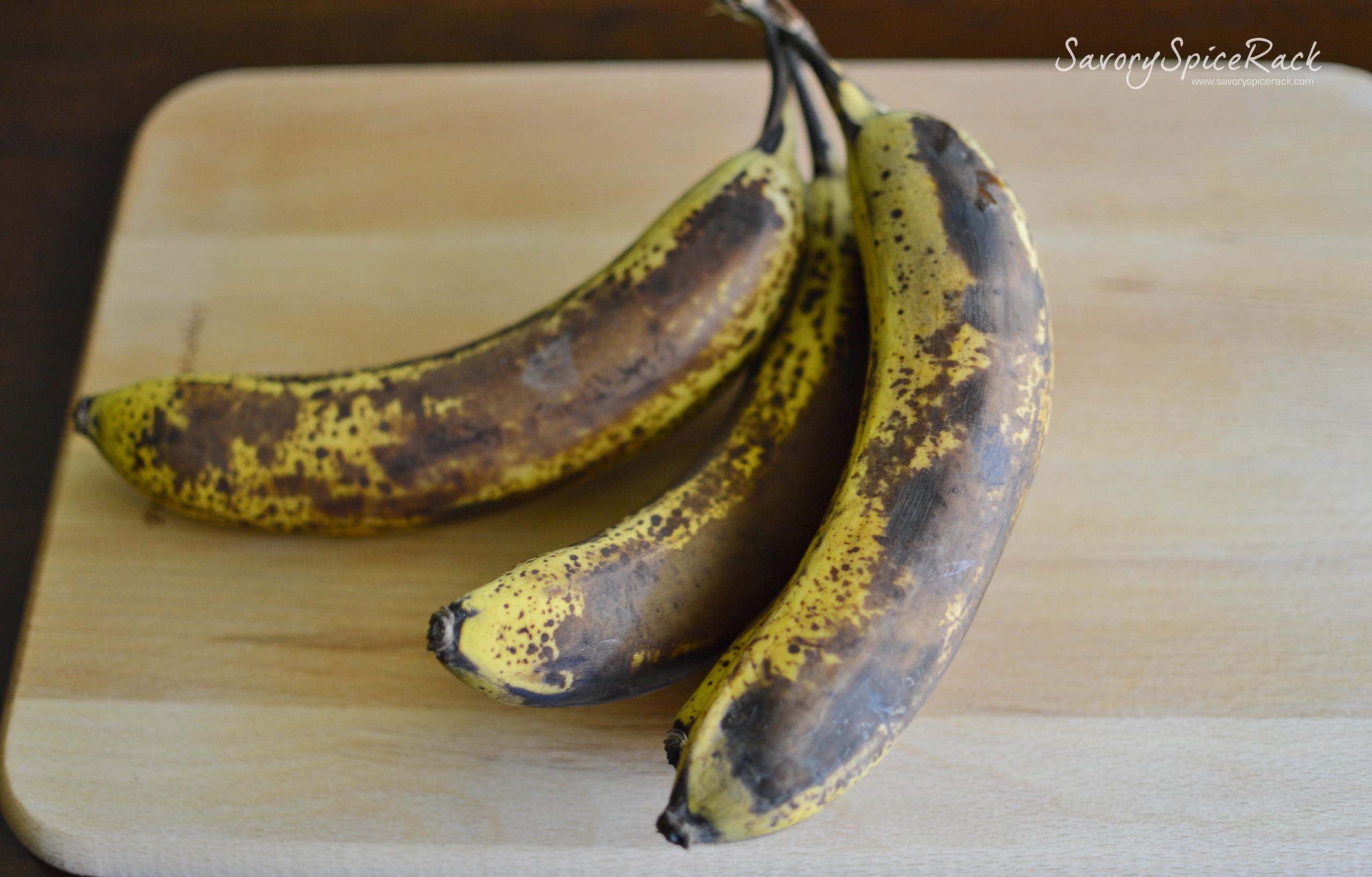 Three perfectly overripe bananas on a wooden board