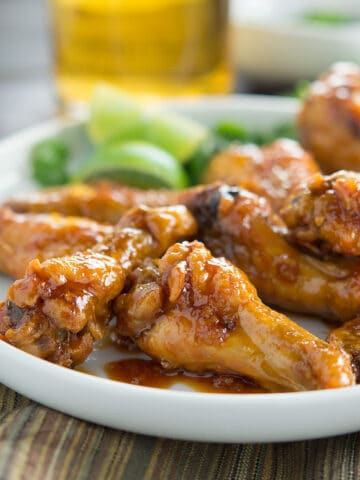 Honey Garlic Chipotle Wings served in a big white plate with a glass of cold drink in the background