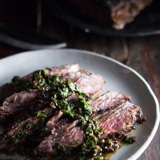 Closeup of the Brazilian Steak with Chimichurri Sauce served on a big plate with a metal fork