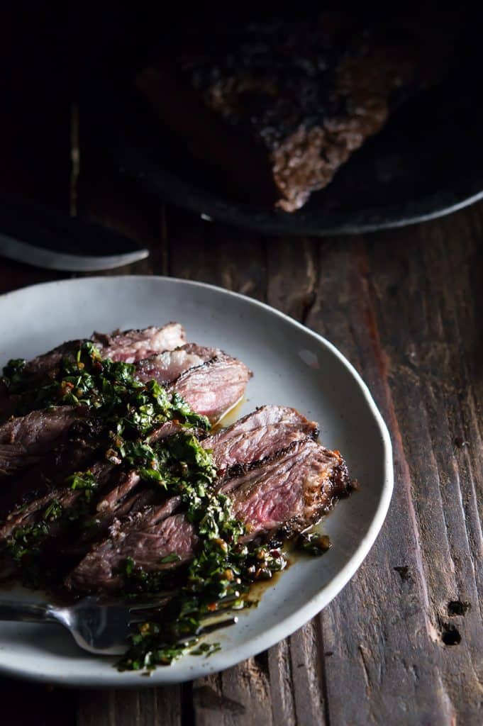 Brazilian Steak with Chimichurri Sauce in a big greyish plate with more food blurred in the background