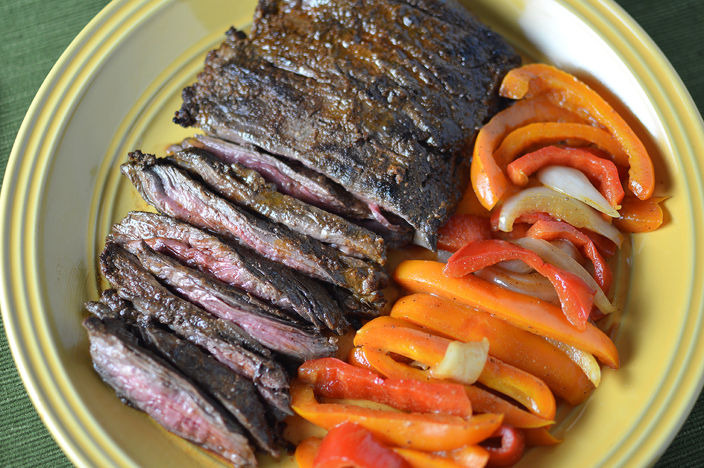 Citrus Marinated Skirt Steaks served with red peppers on a big yellow plate