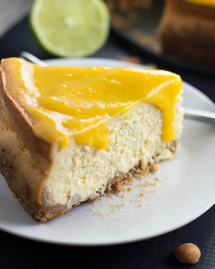 Closeup on the delicious Mango Cheesecake with Macadamia Nut Crust with a piece of lime blurred in the background