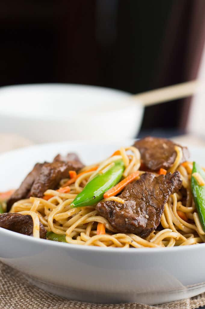 Closeup of a white bowl full of the homemade Stir Fried Thai Red Curry Noodles with Beef with another bowl blurred in the background