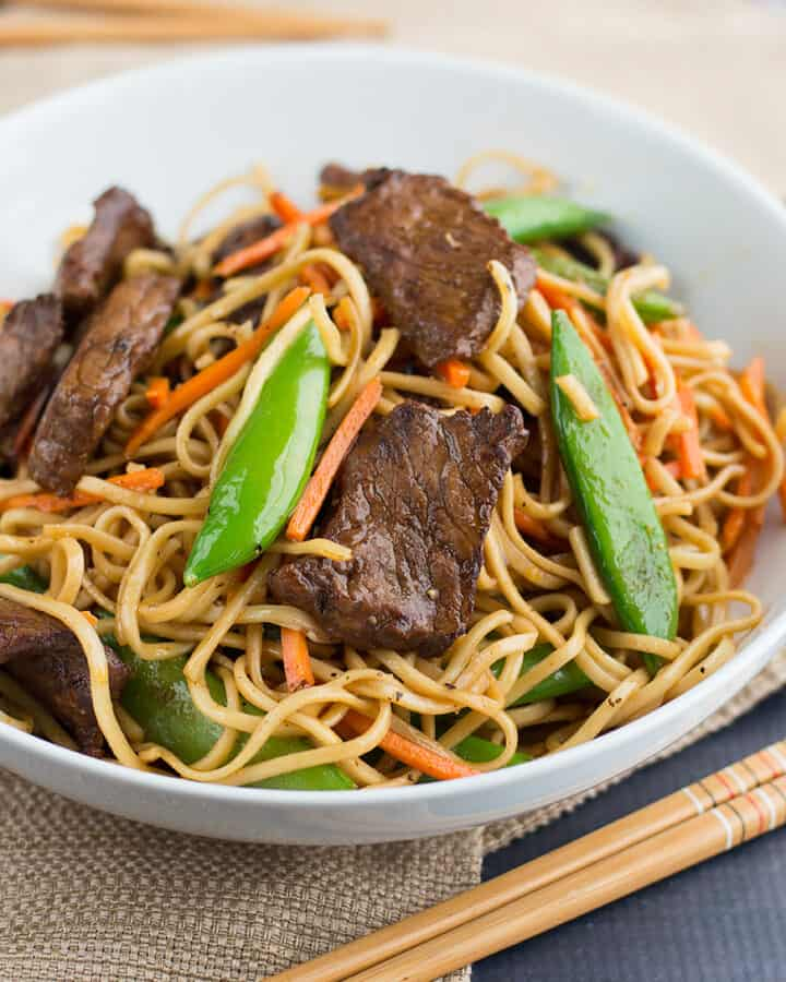 Stir Fried Thai Red Curry Noodles with Beef served with chopsticks