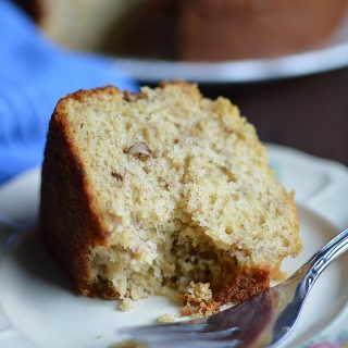 A big piece of the Easy Banana Bread Cake served in a white plate with a metal fork on the side