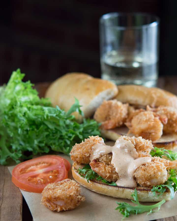 Cajun Panko Crusted Shrimp Po Boys served with greens and tomatoes