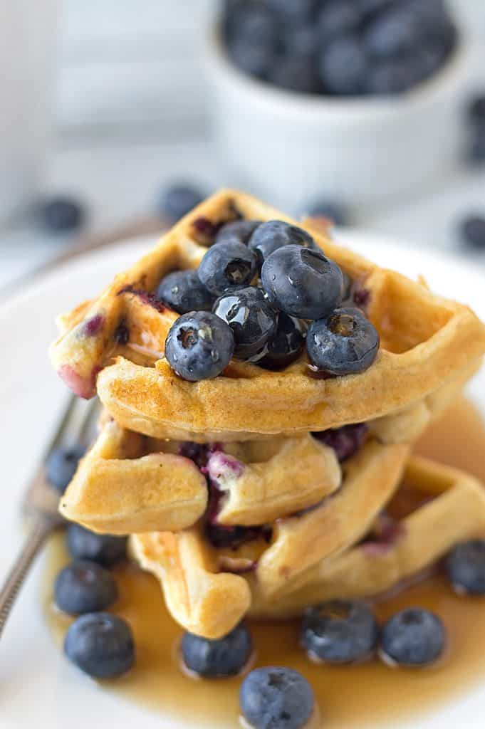A big tower of blueberry ricotta waffles with a lot more blueberries blurred in a bowl in the background