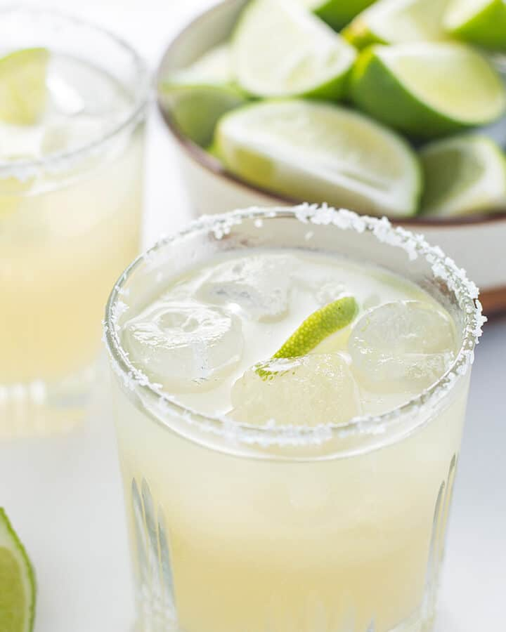 Sparkling Margarita served in a big glass with salt on the rim and plenty of lime wedges in the background
