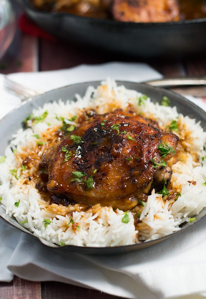 A big grey bowl full of rice with Crispy One Pan Honey Garlic Ethiopian Berbere Chicken Thighs on top