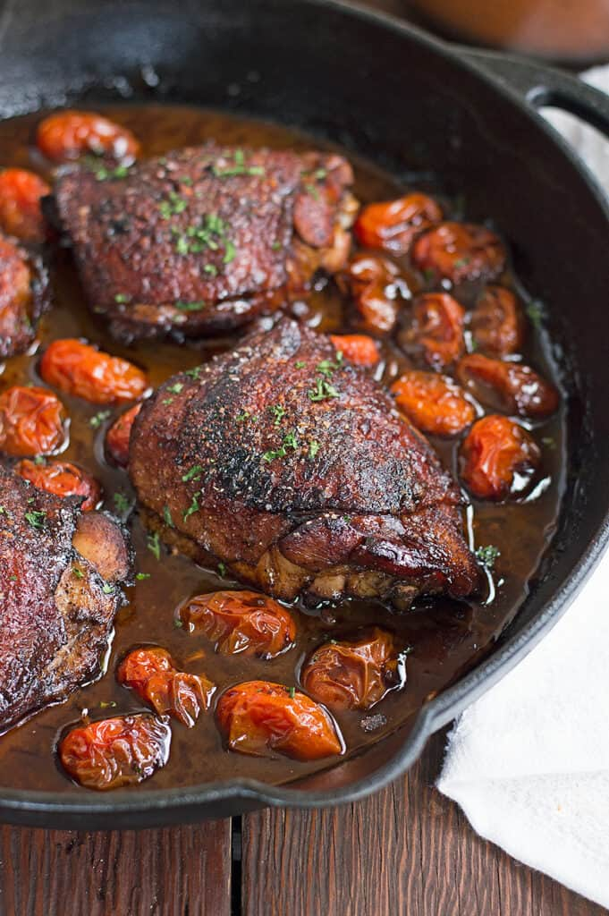 One Pan Roasted Balsamic Chicken and Tomatoes served hot and ready to a wooden table with a white towel on the side