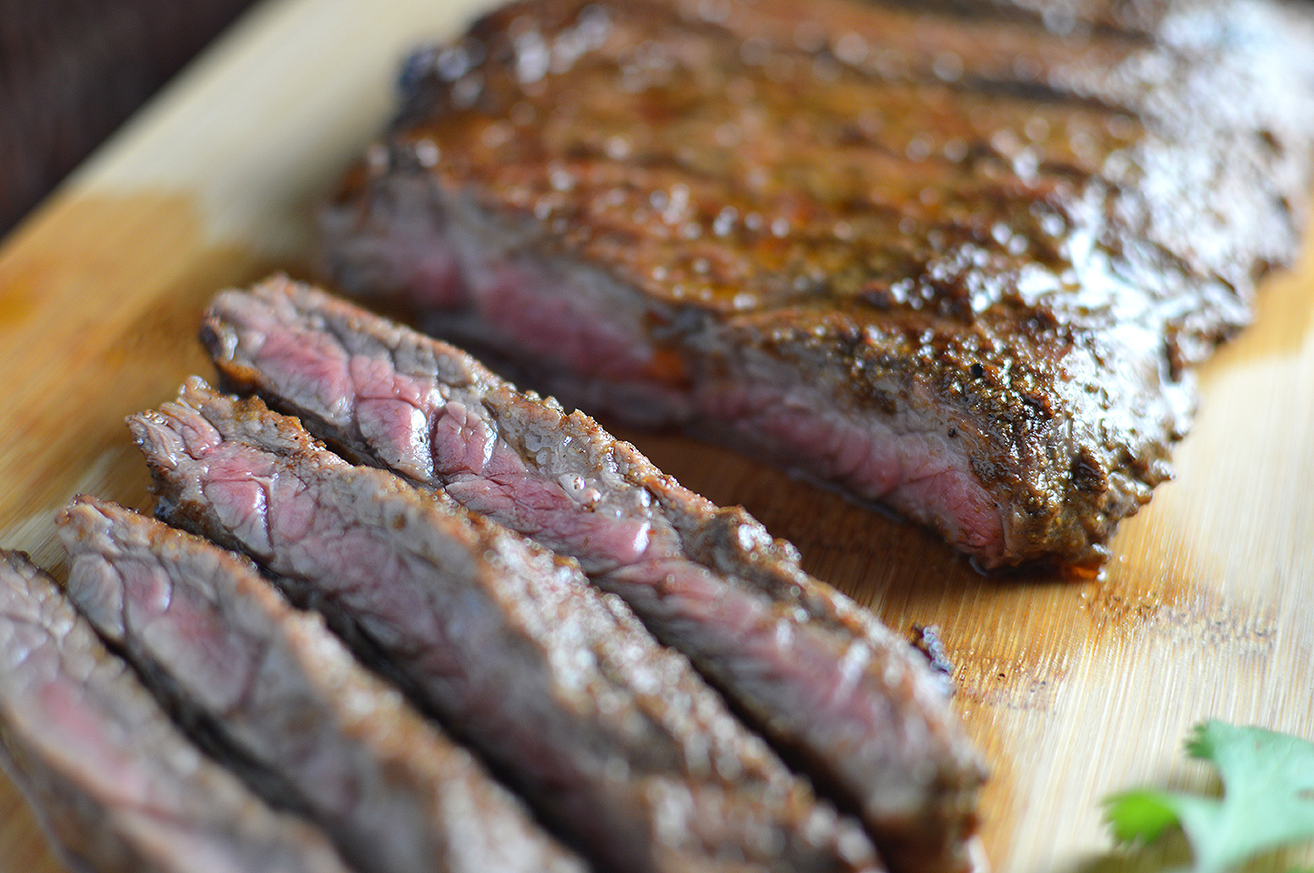 Closeup on the delicious Citrus Marinated Skirt Steaks served on a wooden board