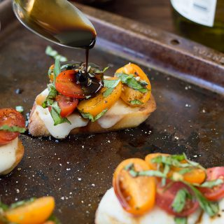 Drizzling sauce on top of each Bruschetta with Cheese served on a metal tray