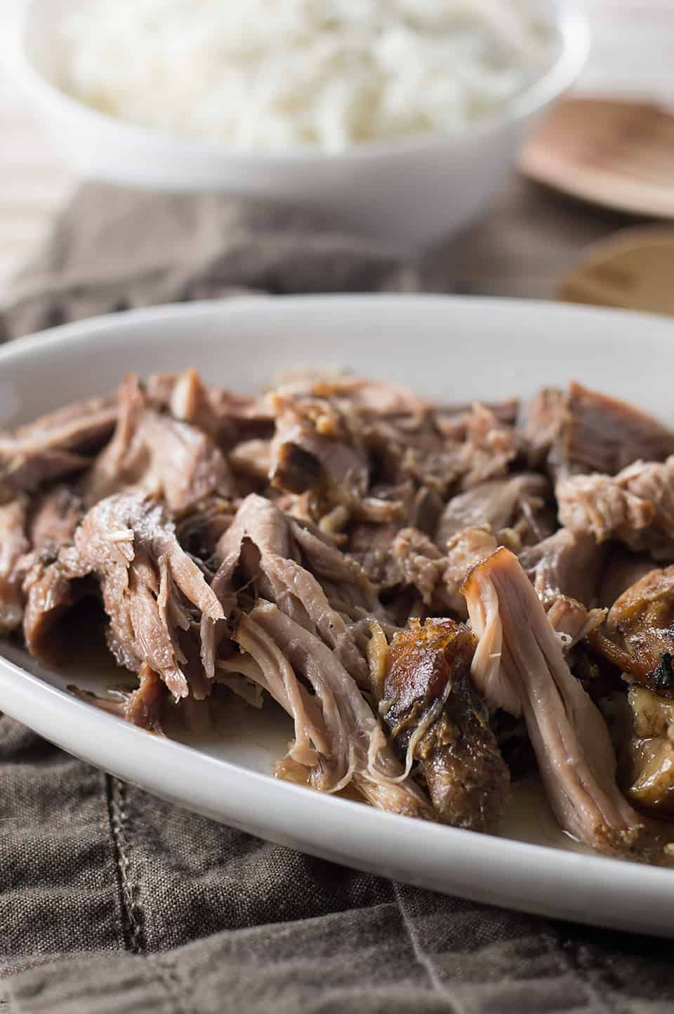 Easy Slow Cooker Kalua Pig looking tender and delicious and served in a big white plate on a table with another side dish blurrred in the background