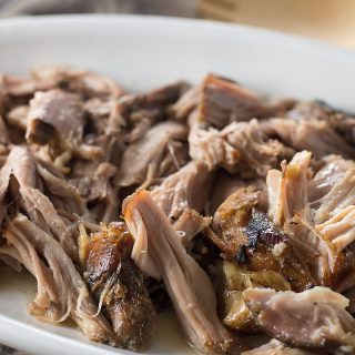 Closeup of the mouthwatering Slow Cooker Kalua Pig looking juicy and absolutely invitin on a white plate with a wooden spoon right next to it