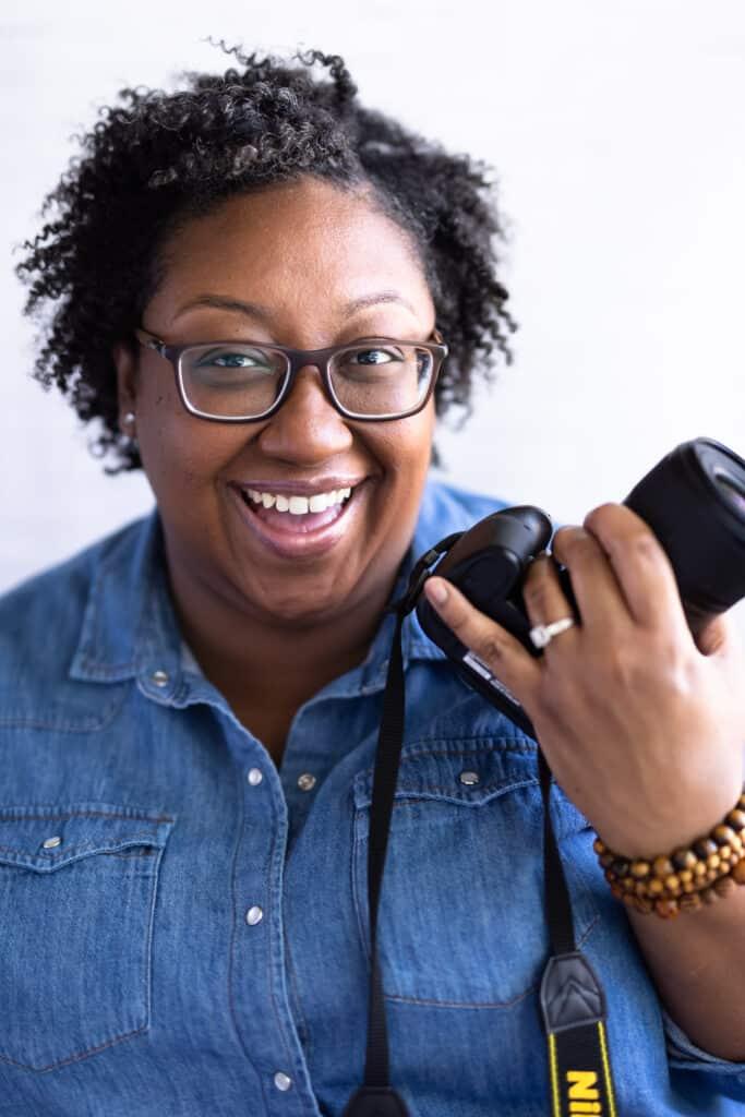 Female wearing blue shirt on holding camera.