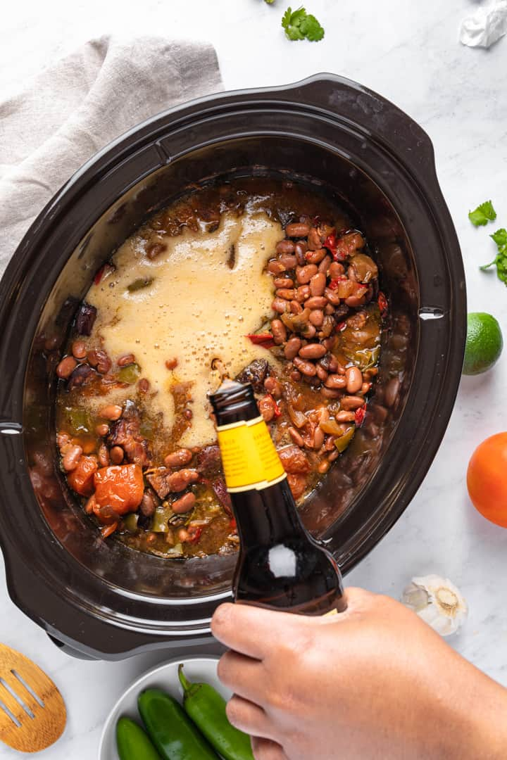 Adding beer to the slow cooker full of the other ingredients slow cooked and ready