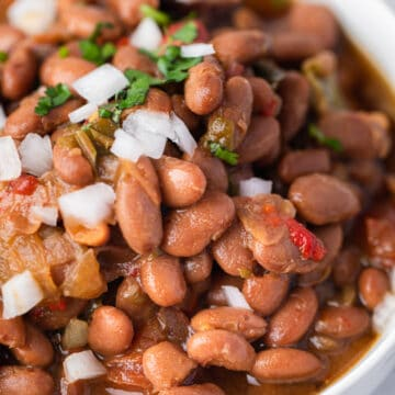 Closeup of the delicious Easy Slow Cooker Charro Beans served in a big white bowl