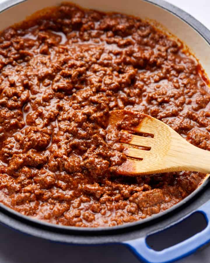 close up photo of chili in blue cast iron pan with wooden spoon