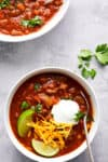 Tuttorosso Tomatoes Traditional Chilli presented in two white bowls and topped with lime wedges and cheese