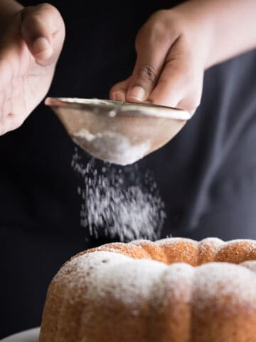 Delicately sprinkling powder over the Amaretto Bundt Cake served in a big white plate on a table