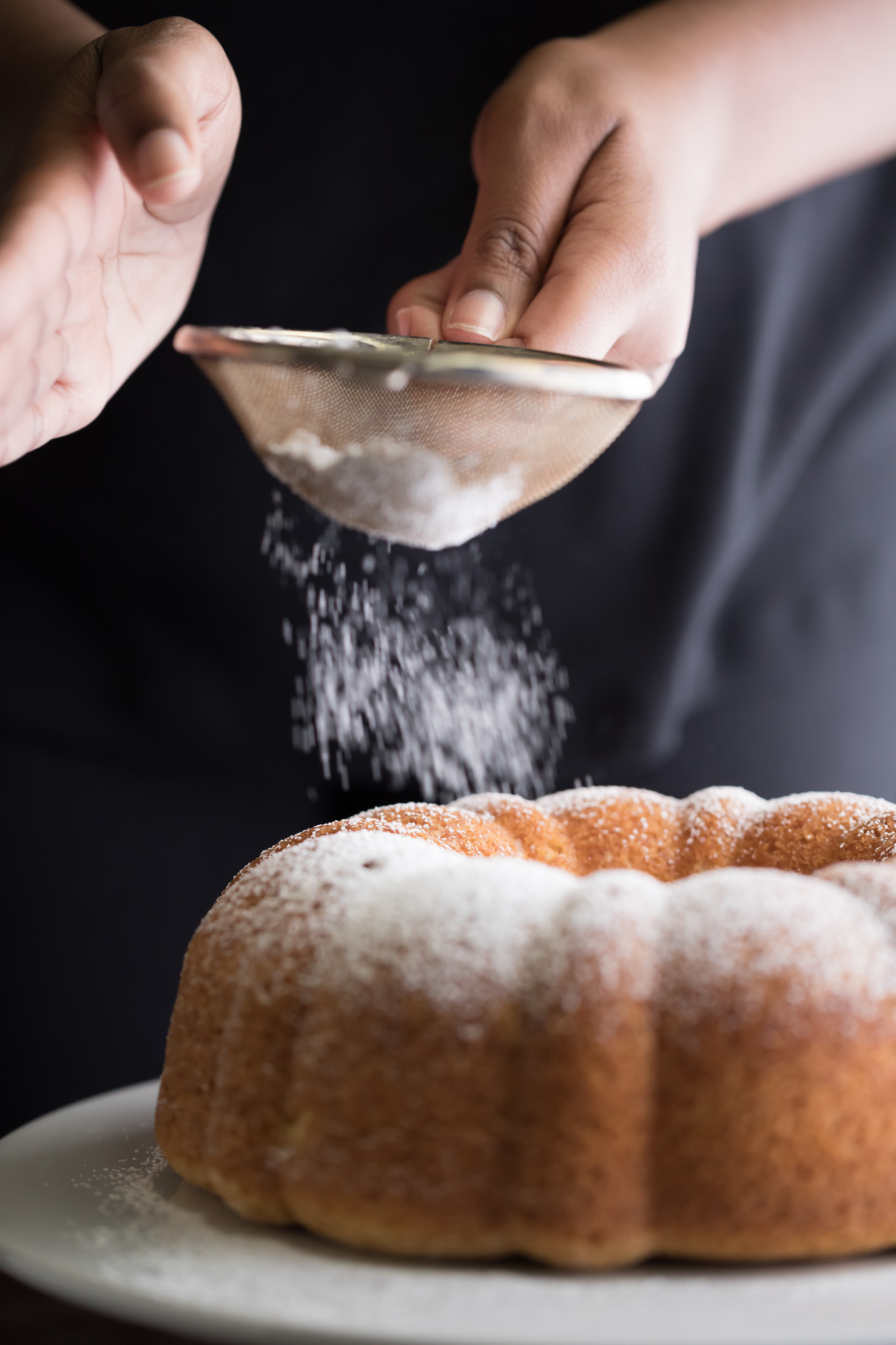 Delicately sprinkling powder over the Amaratto Bundt Cake served in a big white place on a table