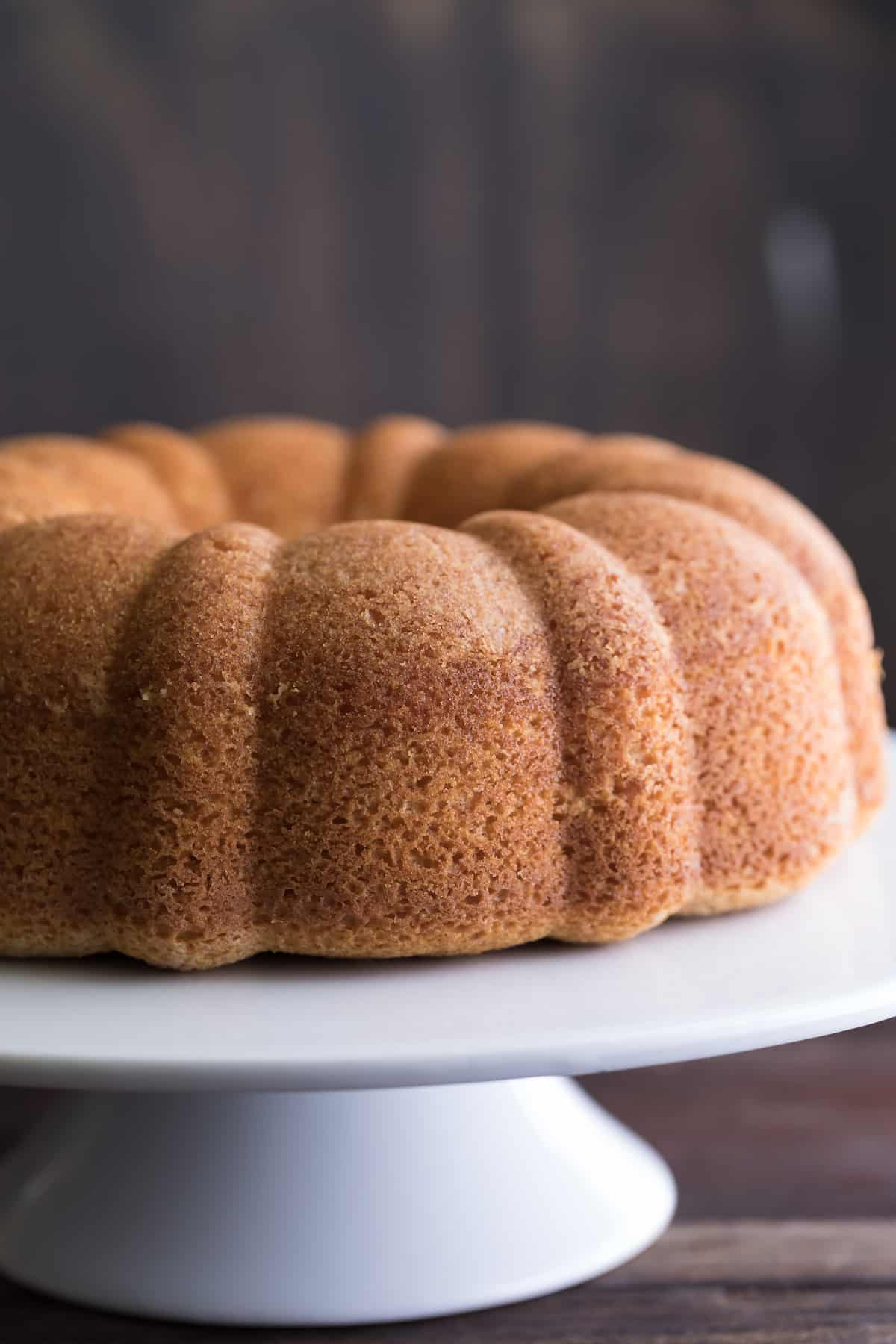 Side closeup on the Delicious Amaratto Bundt Cake with the perfect texture, presented on a cute white stand with a dark background