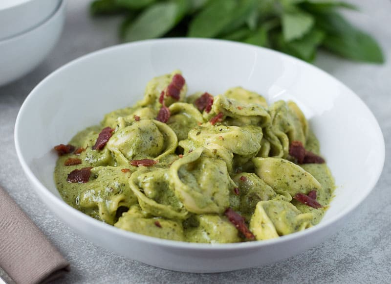 Quick Creamy Pesto Sauce served on a dish in a big white plate with fresh ingredients blurred in the background