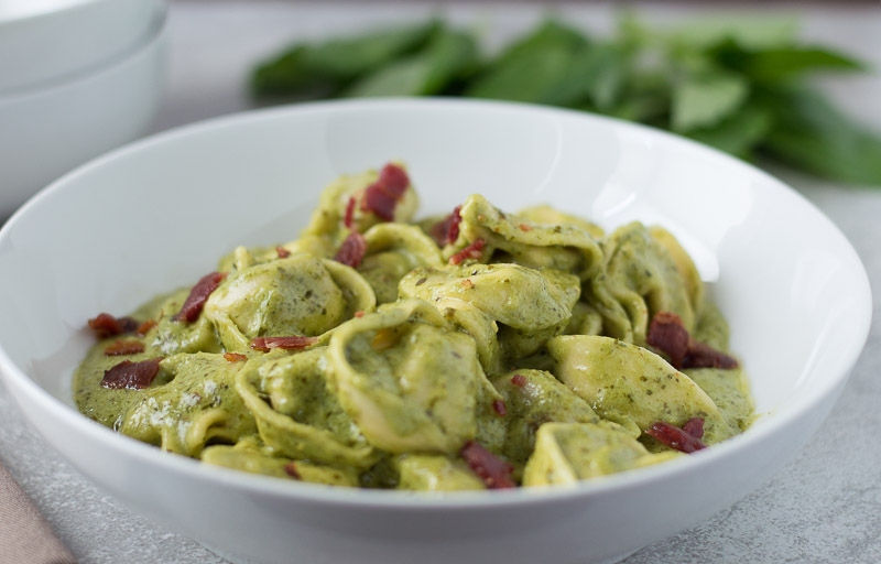 Quick Creamy Pesto Sauce on top of the dish topped with crumbled bacon and shredded Parmesan cheese