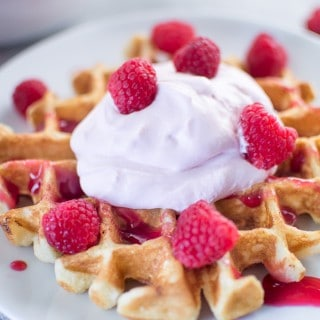 Buttermilk Waffles with Raspberry Champagne Mascarpone Cream served on a white plate in the morning