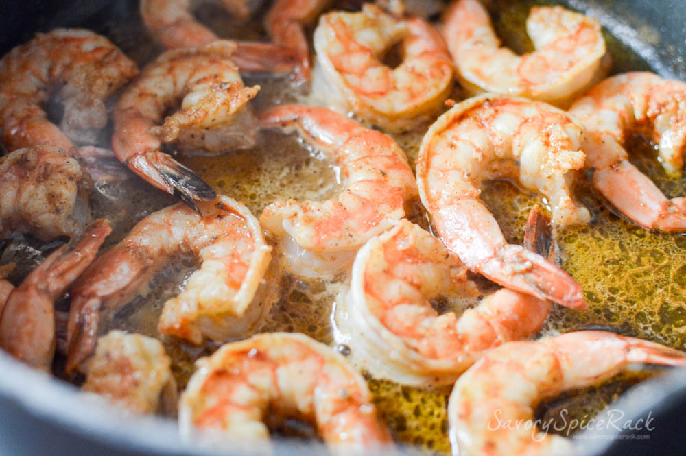 Shrimp getting cooked in oil inside a pan