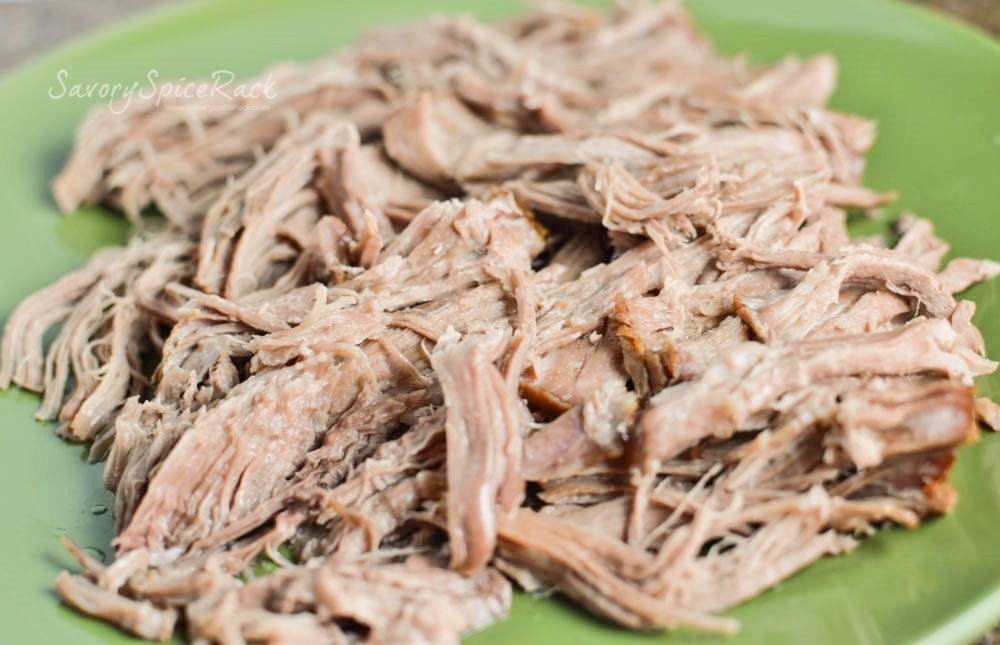 Shredded Slow Cooker Kalua Pig meat on a green plate before serving