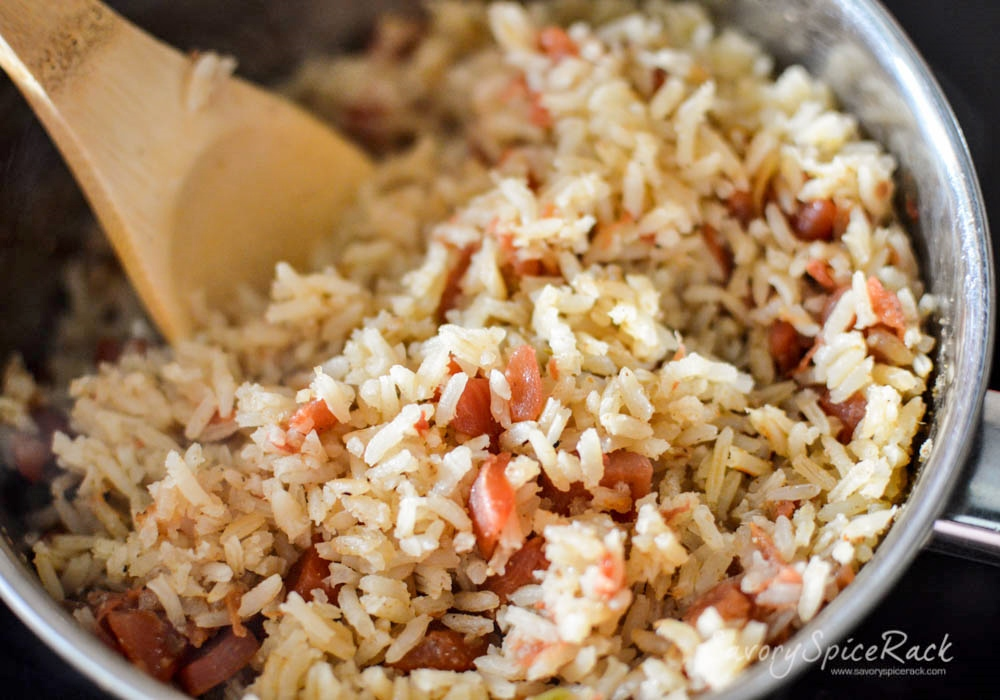 Fluffing rice with a wooden ladle and getting ready to serve it