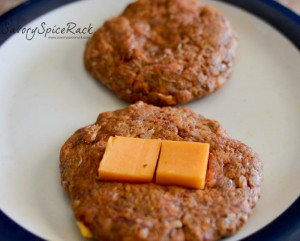 Placing a slice of the cheddar cheese onto three of the hamburger patties