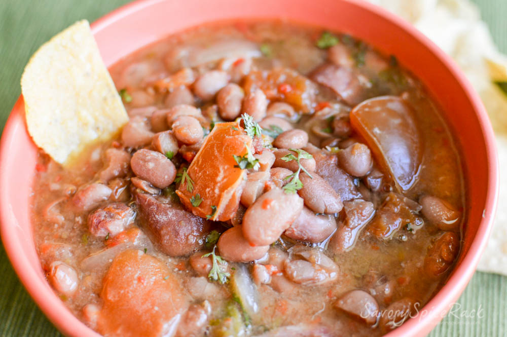 Mouthwatering Easy Slow Cooker Charro Beans with one nacho inside the bowl