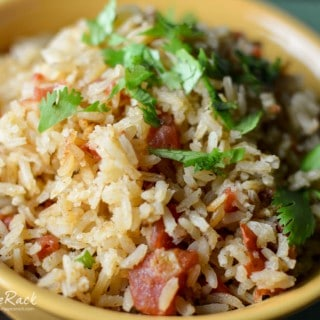 Mexican Rice served in a yellow bowl with bacon and decorated with green herbs