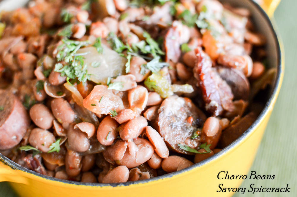 Easy Slow Cooker Charro Beans presented in a yellow pan over the green background
