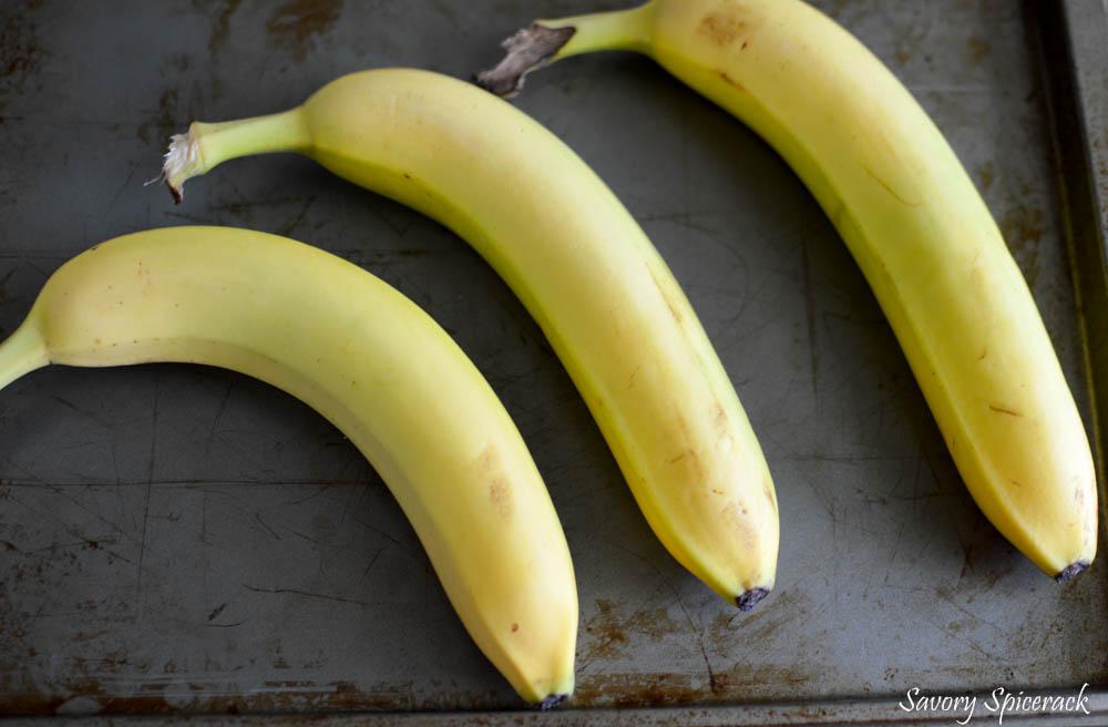 Three fresh bananas on a metal tray